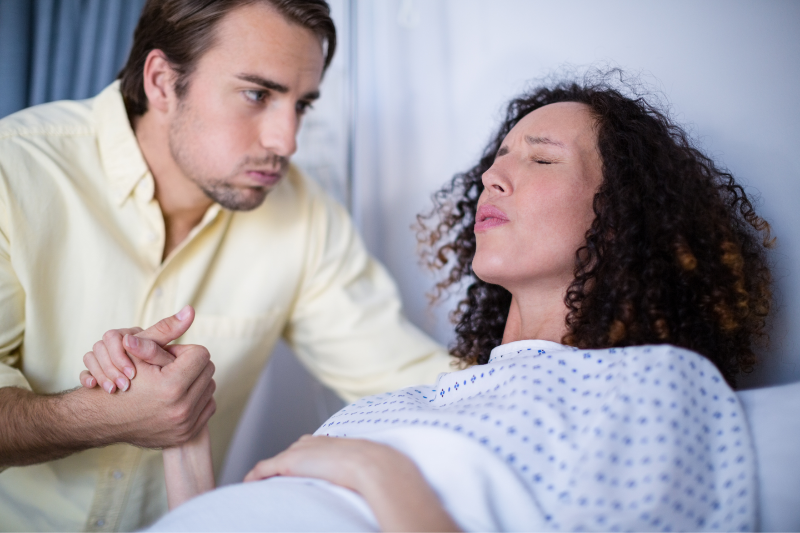 woman laying on bed with contraction pains, her husband is comforting her during her prodromal labor birth